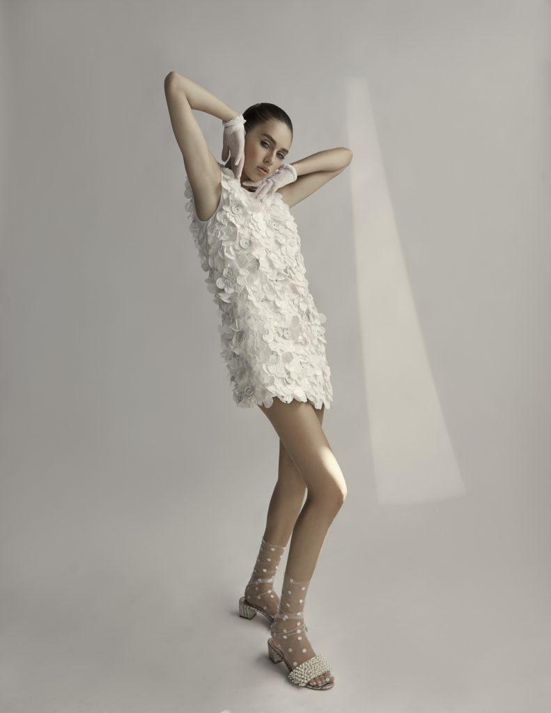 Woman in sleeveless white textured minidress